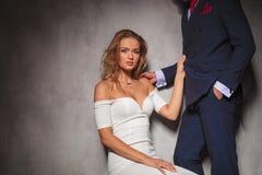 拿着她的恋人的性感的白肤金发的妇女由他的衣服 库存照片
