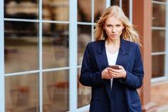 拿着她的手机的年轻人在城市街道 库存图片