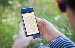 拿着她的智能手机阅读书的草的女孩 库存图片