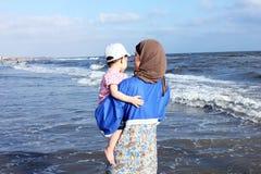 拿着她的海滩的阿拉伯埃及回教母亲女婴在埃及 免版税图库摄影