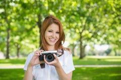 拿着她的照相机的俏丽的红头发人在公园 库存图片