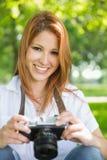 拿着她的照相机的俏丽的红头发人在公园 库存照片