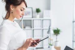 拿着她的片剂的办公室经理的画象,键入,使用接触pda屏幕的Wi-Fi互联网和应用 免版税库存图片