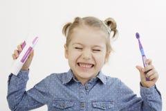 拿着她的牙刷和牙膏的小女孩 免版税库存照片