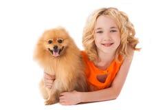 拿着她的狗的小微笑的女孩 库存图片