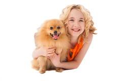 拿着她的狗的小微笑的女孩 免版税库存照片