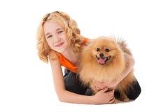 拿着她的狗的小白肤金发的微笑的女孩 免版税库存照片