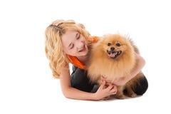 拿着她的狗的小白肤金发的微笑的女孩 免版税图库摄影