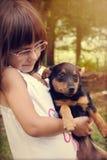 拿着她的狗的愉快的小女孩 库存图片