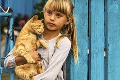 拿着她的猫的小女孩 图库摄影