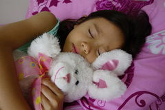 拿着她的玩具兔子的睡觉的亚裔女孩。 图库摄影