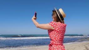 拿着她的电话和为有风风雨如磐的海和波浪照相的年轻女人 她穿帽子和红色礼服有太阳镜的 股票视频