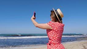拿着她的电话和为有风风雨如磐的海和波浪照相的年轻女人 她穿帽子和红色礼服有太阳镜的 影视素材