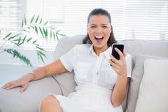 拿着她的电话的恼怒的妇女尖叫对照相机 库存照片