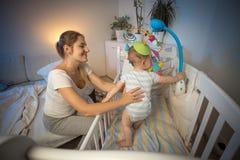 拿着她的男婴的年轻母亲站立在轻便小床在晚上 库存照片