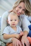 拿着她的男婴的年轻母亲 免版税图库摄影