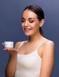 拿着她的皮肤的微笑的俏丽的妇女化妆奶油 库存照片