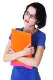 拿着她的笔记的年轻沉思学生 库存图片