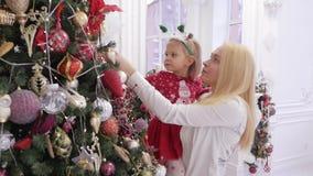 拿着她的胳膊的妇女一个小女儿在一棵装饰的圣诞树 影视素材