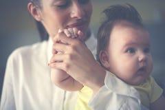 拿着她的胳膊的愉快的母亲女婴 免版税库存图片