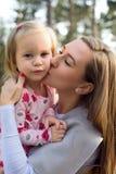 拿着她的胳膊的逗人喜爱的小孩女孩女儿和给她在面颊的年轻母亲一个亲吻 免版税库存图片