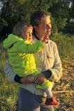 拿着她的胳膊的年轻可爱的年轻母亲一个小女孩在日落光 走在秋天温暖平衡户外在太阳 免版税库存图片