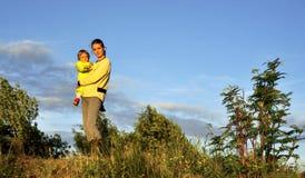 拿着她的胳膊的年轻可爱的年轻母亲一个小女孩在日落光 走在秋天温暖平衡户外在太阳 库存图片