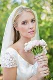 拿着她的花束的平安的新娘头戴看照相机的面纱 免版税库存图片