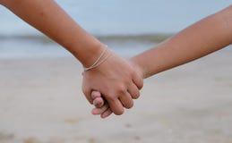 拿着她的brother& x27的姐妹; 在海滩的s手 免版税库存图片