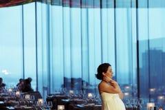 拿着她的nack作白日梦在一个空的咖啡馆的怀孕的新娘 图库摄影