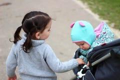 拿着她的sister& x27的女孩;在摇篮车的s手 免版税库存照片