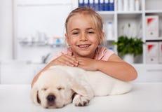 拿着她睡觉小狗的愉快的女孩在兽医医生办公室 免版税库存照片