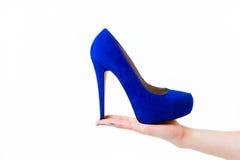 拿着妇女鞋子的手 免版税库存照片