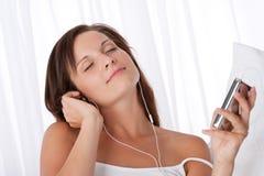 拿着妇女年轻人的听的mp3音乐播放器 免版税库存图片