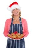 拿着姜饼人的板材圣诞老人帽子的妇女 库存照片