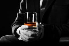 拿着威士忌酒的严肃的商人特写镜头说明行政特权概念 库存图片