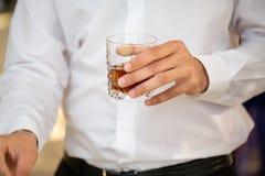 拿着威士忌酒的人玻璃 免版税库存图片