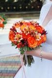 拿着婚姻的橙色花束用野玫瑰果、Smokebush和黄色水芋百合的新娘 库存照片