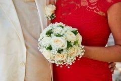 拿着婚姻的花束的一件红色礼服的一名妇女 免版税库存照片