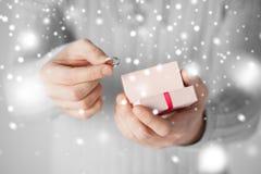 拿着婚戒和礼物盒的人 免版税库存图片