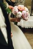 拿着婚礼玫瑰bouq的典雅的白色礼服的华美的新娘 库存照片