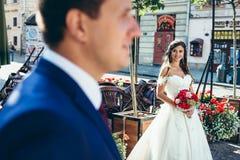 拿着婚礼花束和看被弄脏的可爱的微笑的深色的新娘的水平的画象 免版税库存图片