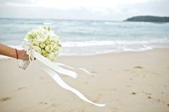 拿着婚礼花束有海滩背景的手 免版税库存图片