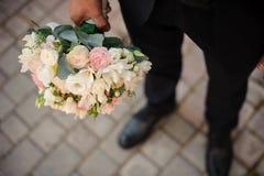 拿着婚礼花束的一双黑衣服和经典鞋子的新郎 库存图片