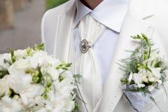 拿着婚礼花束的一套白色衣服的新郎 免版税库存照片