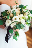 拿着婚礼花束的一套豪华婚礼礼服的新娘用一条黑丝带装饰由玫瑰做成 免版税库存照片