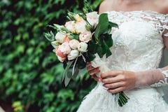 拿着婚礼花束的一套豪华婚礼礼服的新娘由玫瑰做成 库存图片