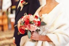 拿着婚礼花束的一套豪华婚礼礼服的新娘由玫瑰做成 免版税库存照片