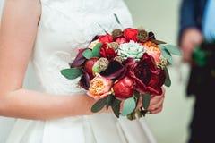 拿着婚礼花束的一套豪华婚礼礼服的新娘由红色牡丹制成 图库摄影