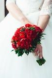 拿着婚礼花束的一套豪华婚礼礼服的新娘由英国兰开斯特家族族徽和牡丹制成 免版税库存照片